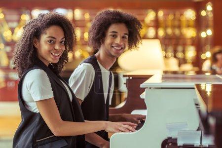 Photo pour Vue latérale d'un beau jeune couple afro-américain en gilet classique souriant et jouant du piano dans un magasin de musique - image libre de droit