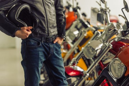 Photo for Man in black leather jacket is holding a helmet and examining motorbikes in a motorbike salon, close-up - Royalty Free Image