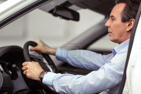 Photo pour Vue latérale de beau milieu d'âge homme d'affaires est assis dans une nouvelle voiture dans un salon de l'automobile - image libre de droit
