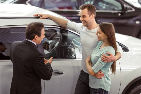 Handsome middle aged salesman is showing a car to ...