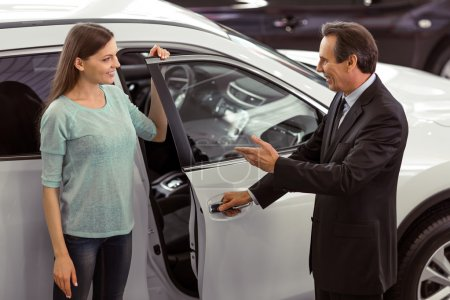 Photo for Handsome middle aged salesman is presenting a car to beautiful young woman in a motor show - Royalty Free Image