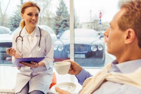Photo pour Belle femme médecin en robe blanche parle avec un beau patient d'âge moyen, prendre des notes et sourire. L'homme tient une tasse - image libre de droit