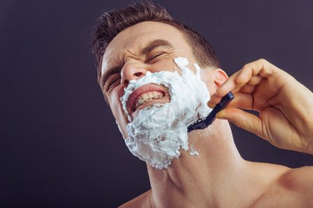 Portrait of handsome man getting hurt while shavin...
