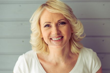 Photo for Portrait of beautiful mature woman looking at camera and smiling, against gray background - Royalty Free Image