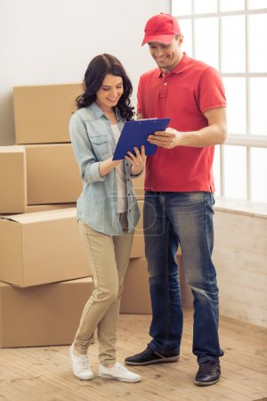 Photo for Attractive young woman and handsome delivery worker are signing documents for moving, cardboard boxes in the background - Royalty Free Image