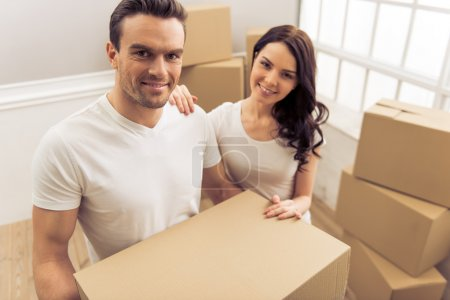 Photo for Attractive young couple is moving, looking at camera and smiling while standing among cardboard boxes. Man is holding a box - Royalty Free Image