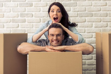 Photo for Happy young couple is moving, looking at camera and smiling, standing among cardboard boxes. Man is leaning on box while woman is leaning on him - Royalty Free Image