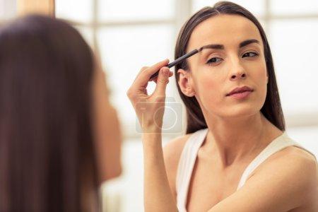 Photo pour Belle fille fait un maquillage, retoucher les sourcils tout en regardant le miroir - image libre de droit