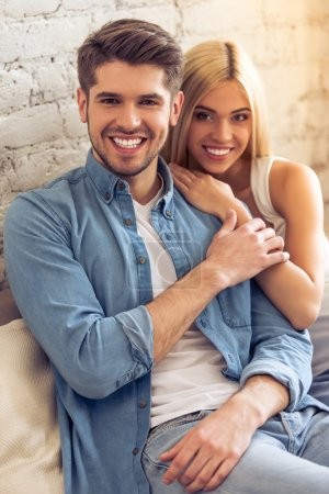 Photo for Beautiful young couple is hugging, looking at camera and smiling while sitting on sofa at home - Royalty Free Image