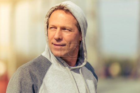 Photo for Portrait of handsome middle aged man in sports uniform looking away and smiling during morning run - Royalty Free Image