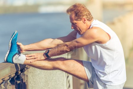 Photo for Side view of handsome middle aged man in sports uniform stretching leaning on bridge during morning run - Royalty Free Image