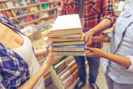 Photo for Cropped image of young students holding a pile of books while standing in the book shop - Royalty Free Image