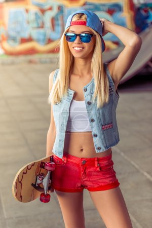 Photo for Beautiful blonde girl in cap and glasses is looking at camera and smiling while standing with her skateboard in skate park - Royalty Free Image