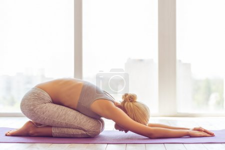 Photo for Side view of beautiful young woman in sports wear stretching on a yoga mat against window - Royalty Free Image