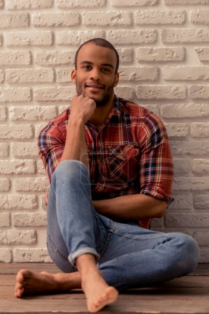 Photo for Handsome Afro American man in casual clothes is looking at camera and smiling while sitting on the floor against white brick wall - Royalty Free Image