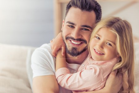 Photo for Portrait of handsome father and his cute daughter hugging, looking at camera and smiling - Royalty Free Image
