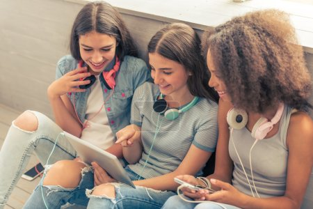 Photo for Group of teenage girls with headphones is using gadgets, talking and smiling while sitting on the floor - Royalty Free Image