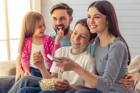 Photo pour De beaux jeunes parents, leur fille et leur fils regardent la télévision, mangent du pop-corn et sourient, assis sur un canapé à la maison. Maman utilise une télécommande - image libre de droit
