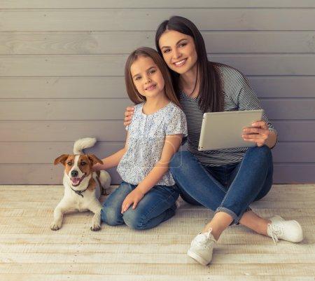 Photo pour Petite fille mignonne et sa belle jeune mère regardent la caméra et sourient tout en posant avec leur chien. Maman utilise un comprimé - image libre de droit