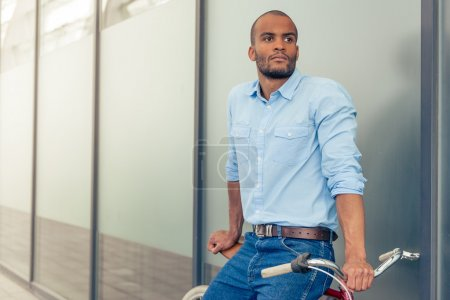 Photo for Handsome young Afro American man in casual clothes is looking away while leaning on his bike, standing outdoors - Royalty Free Image