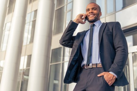 Photo for Handsome young Afro American businessman in classic suit talking on the mobile phone and smiling, standing outdoors near the office building - Royalty Free Image