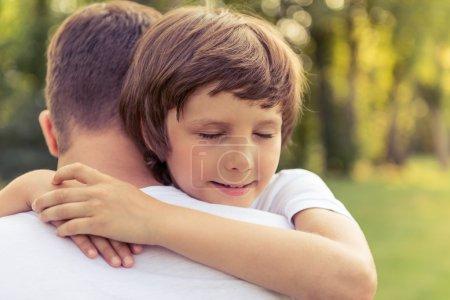 Photo pour Portrait de mignon petit garçon étreignant son père tout en se reposant à l'extérieur - image libre de droit
