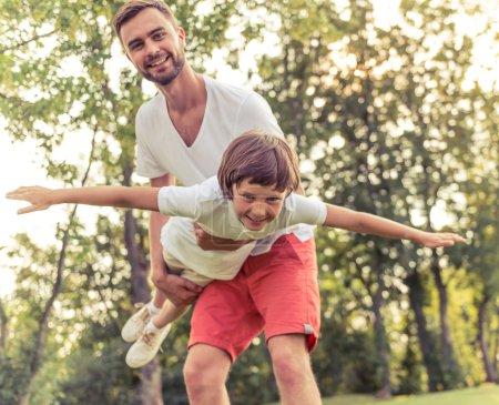 Photo pour Beau jeune papa et son mignon petit fils sont caméra regardant et souriant tout en jouant dans le parc. Père tient son fils dans les bras, le garçon est imitant un avion - image libre de droit