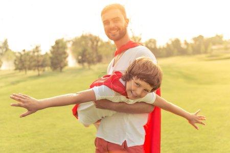 Photo pour Beau jeune papa et son mignon petit garçon vêtu comme super-héros sont à la recherche de la caméra et souriant tout en jouant dans le parc. Père tient son fils dans les bras - image libre de droit