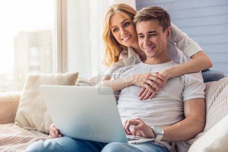 Photo pour Beau jeune homme d'affaires en vêtements décontractés utilise un ordinateur portable et souriant, assis sur le canapé à la maison tandis que sa belle fille le serre dans ses bras derrière - image libre de droit