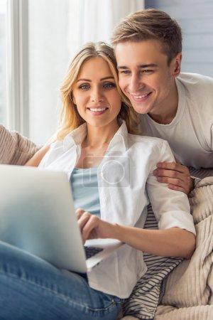 Photo pour Belle jeune femme en vêtements décontractés utilise un ordinateur portable et souriant, assis sur le canapé à la maison tandis que son beau petit ami la serre dans ses bras derrière - image libre de droit