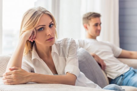 Photo for Young couple quarrels. Beautiful young woman is sitting sad on couch at home, her boyfriend is sitting in the background - Royalty Free Image