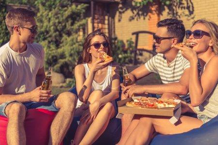 Photo pour Jeunes belles personnes en vêtements décontractés et lunettes de soleil mangent de la pizza, communiquent et sourient, assis sur des chaises de sac de haricot tout en se reposant à l'extérieur - image libre de droit