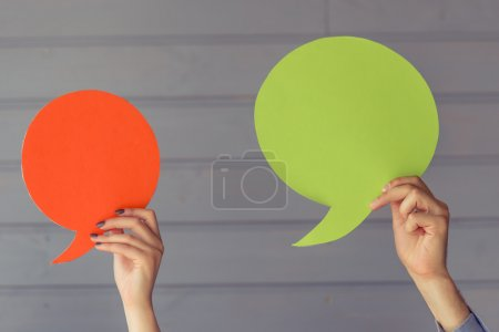 Photo for Hands are holding colorful speech bubbles before gray wall - Royalty Free Image