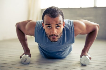 Photo pour Beau sportif afro-américain tient des haltères et fait des push ups tout en travaillant dehors à la maison - image libre de droit