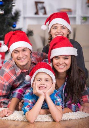 Photo pour Portrait de famille amicale regardent la caméra le soir de Noël. Arbre de Noël. Chapeau de Père Noël . - image libre de droit