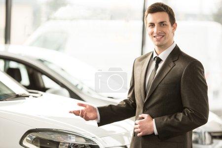 Photo pour Consultant jeune homme dans la salle d'exposition est debout près de voiture. Vue de dessus. - image libre de droit