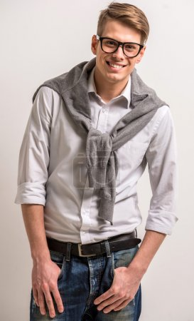 Photo for Handsome smiling man in casual wear standing and looking at camera on grey background. - Royalty Free Image