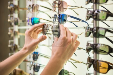 Photo for Young man (only hands) at optician with glasses is looking for sunglasses. - Royalty Free Image