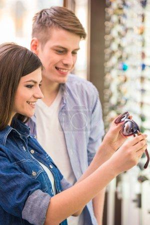 Photo pour Jeune couple chez opticien dans le magasin, ils recherchent des lunettes . - image libre de droit
