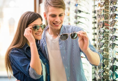 Photo for Young couple at optician in the store, they looking for glasses. - Royalty Free Image
