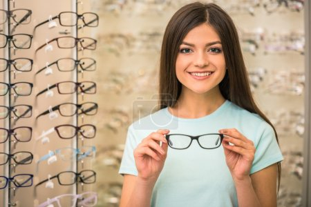 Photo for Young woman is choosing a glasses in optician store. - Royalty Free Image