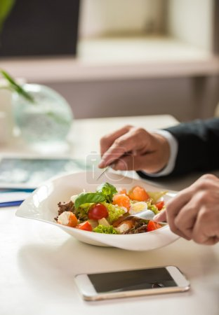 Photo for Close-up of businessman hands holding knife and fork over salad during business lunch. - Royalty Free Image