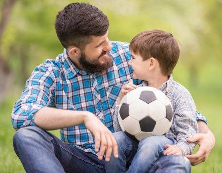 Photo pour Jeune père avec son petit fils s'amuser sur le terrain de football . - image libre de droit