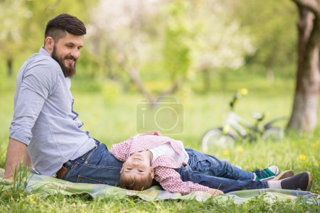 Photo for Happy family having fun outdoors in spring garden. Father playing with child. Family concept. - Royalty Free Image