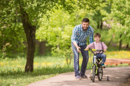 Photo for Young father teaching son to ride bicycle in summer park. - Royalty Free Image