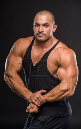 Photo for Muscular young man in studio on dark background shows the different movements and body parts. - Royalty Free Image