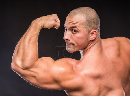 Photo for Bodybuilder in good shape against a dark background. Man posing, showing his muscle definition. - Royalty Free Image