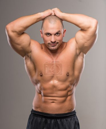 Photo for Young sexy handsome athletic man with naked torso on gray background. - Royalty Free Image