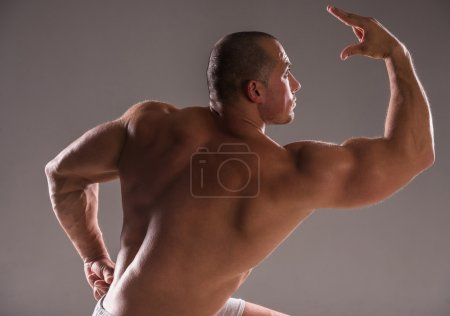 Photo for Beautiful muscular man bodybuilder posing back over dark background. - Royalty Free Image