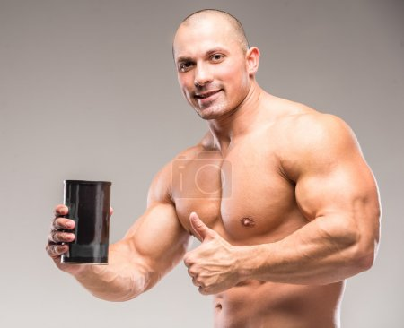 Photo for Muscular bodybuilder drinking protein on a dark background. - Royalty Free Image